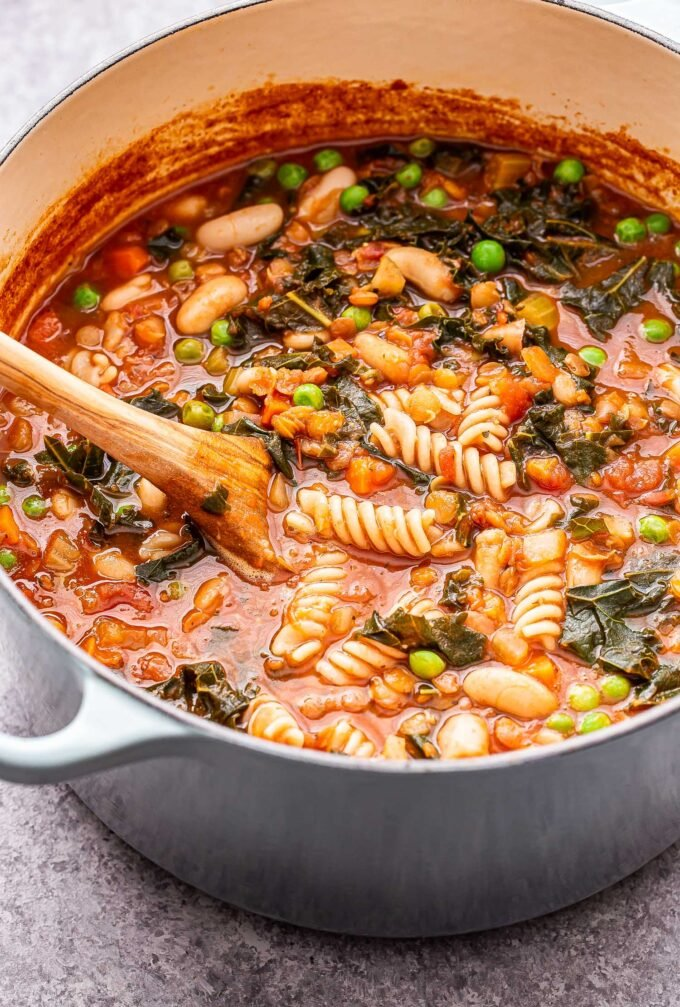 Lentil Minestrone Soup in a large pot with a wooden spoon.