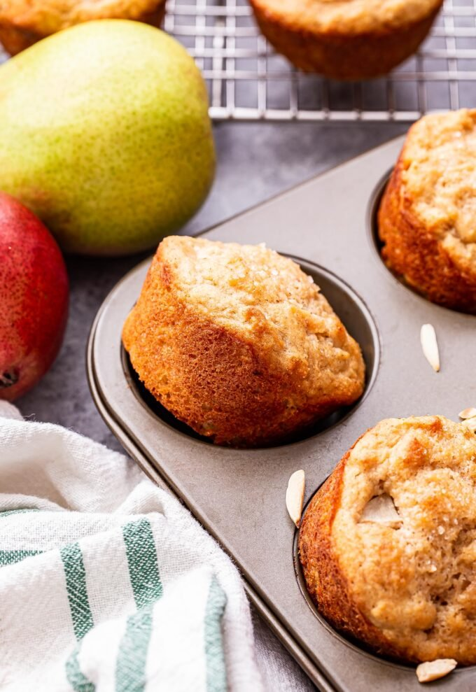 Pear Ginger Muffins in a muffin pan with pears behind the pan.