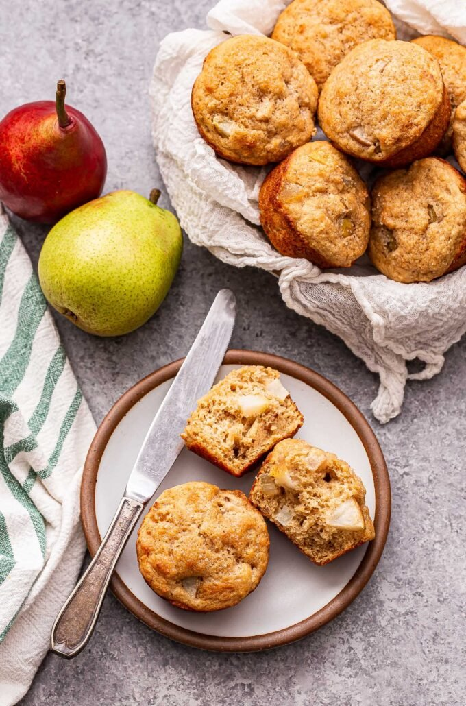 Two Pear Ginger Muffins on a white plate with a basket of the muffins and two pears behind them.