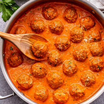 Turkey Meatballs in Roasted Red Pepper Sauce in a metal skillet with a wooden spoon in it.