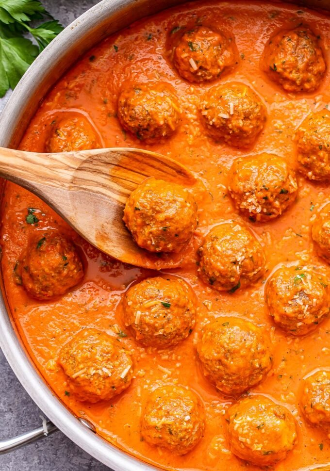 wooden spoon holding up one of the Turkey Meatballs in Roasted Red Pepper Sauce