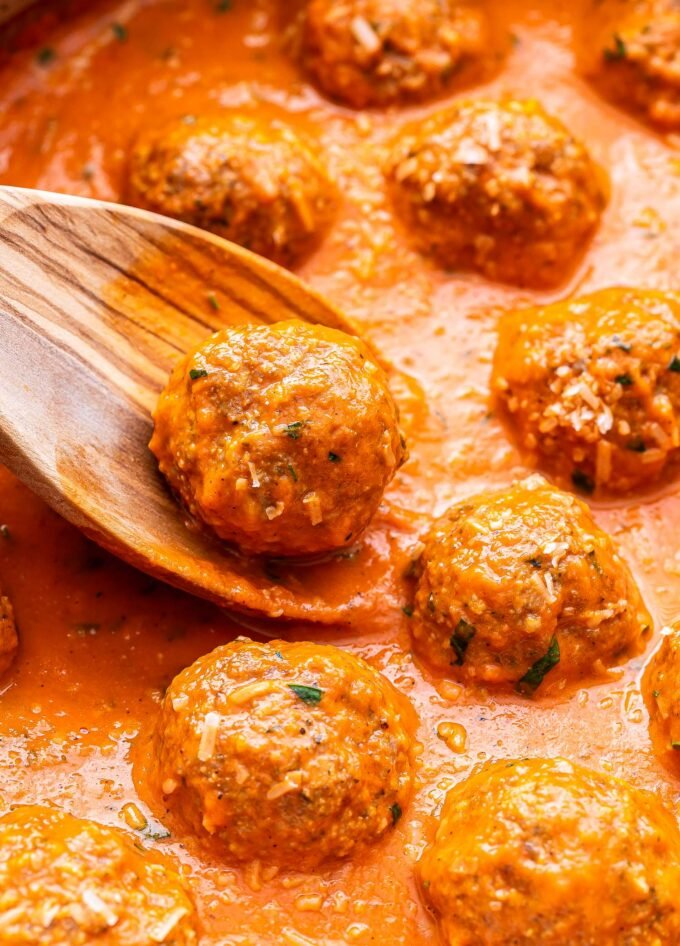closeup of a wooden spoon holding a Turkey Meatball in Roasted Red Pepper Sauce