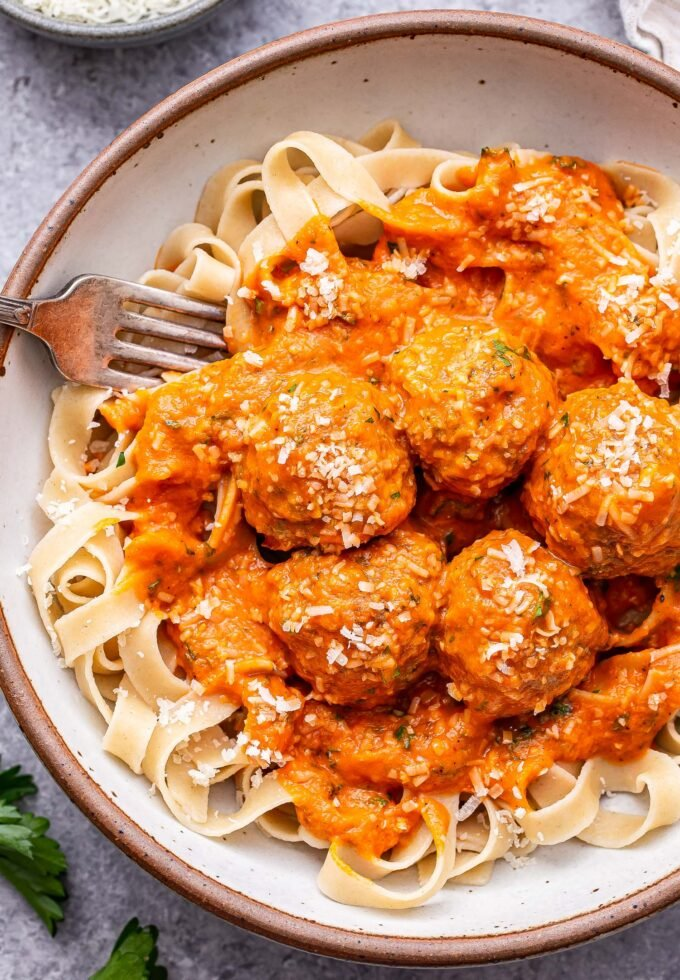 Turkey Meatballs in Roasted Red Pepper Sauce on top of fettuccine in a white bowl.