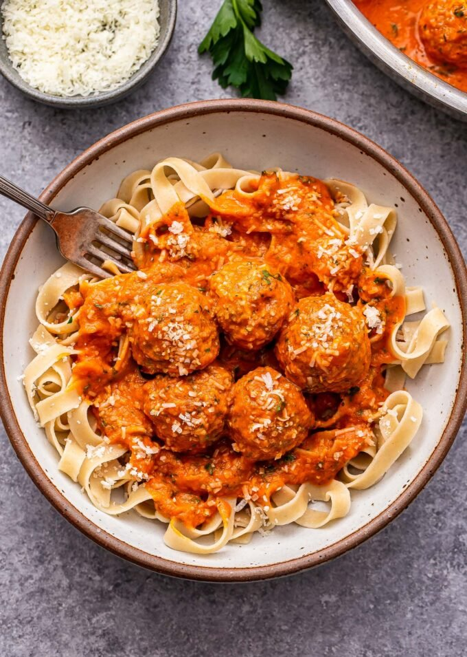 Turkey Meatballs in Roasted Red Pepper Sauce on top of fettuccine in a white bowl with a fork in it.