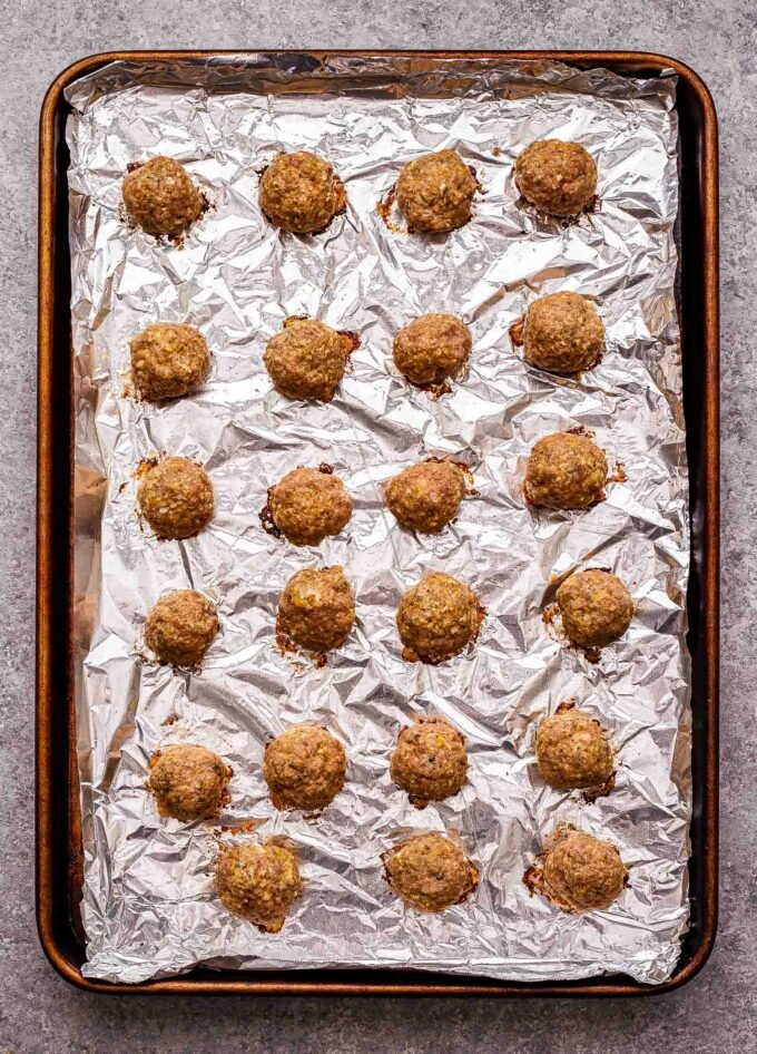 Baked turkey meatballs on a sheet pan lined with foil.