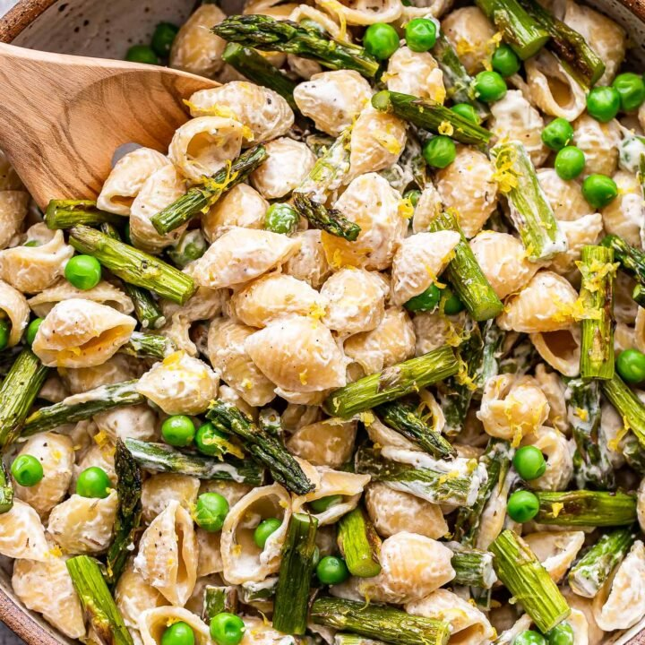 Asparagus goat cheese pasta in a white bowl with a wooden spoon.