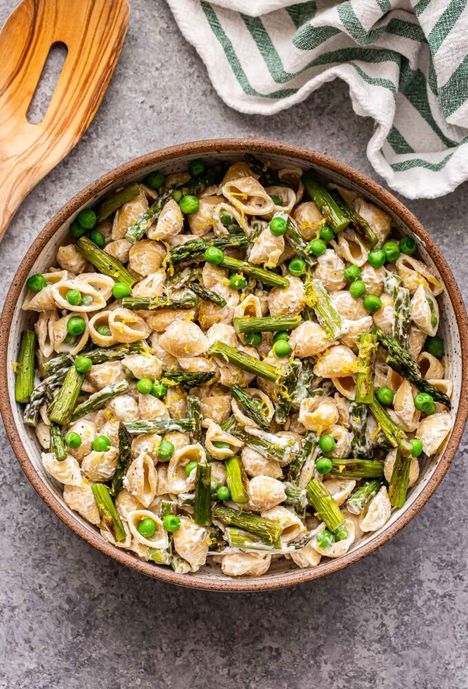 Asparagus goat cheese pasta in a white bowl with a dish towel and wooden serving spoon behind the bowl.