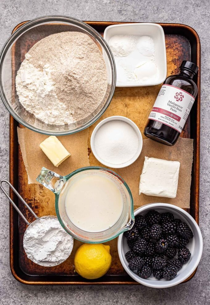 ingredients used to make blackberry vanilla sweet rolls on a sheet pan.