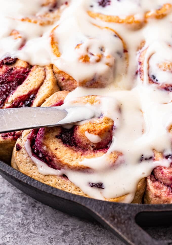 A knife spreading cream cheese frosting on top of a Blackberry Vanilla Sweet Roll.