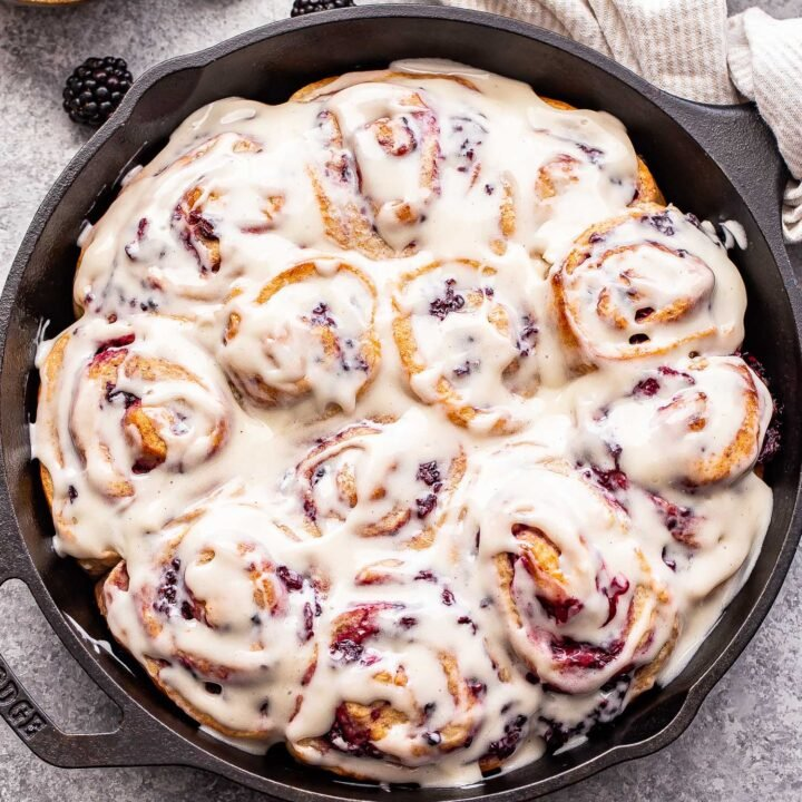 12 Blackberry Vanilla Sweet Rolls in a cast iron skillet topped with cream cheese frosting.