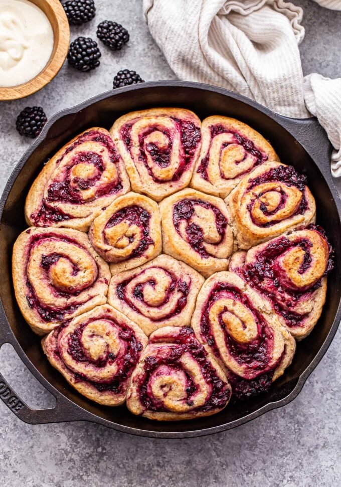 Unfrosted Blackberry Vanilla Sweet Rolls in a black cast iron skillet with a bowl of cream cheese frosting behind them.
