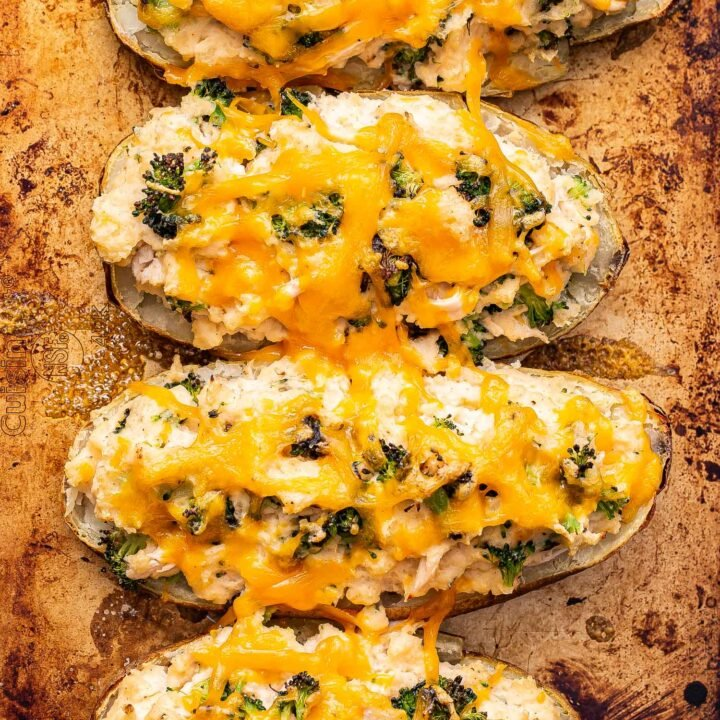 Four Broccoli cheddar chicken twice baked potatoes on a sheet pan.