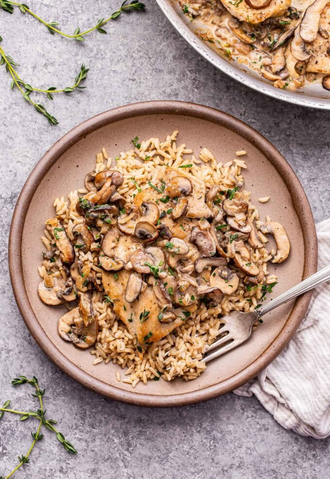 Creamy Mushroom Chicken on top of rice on a brown plate with a fork.