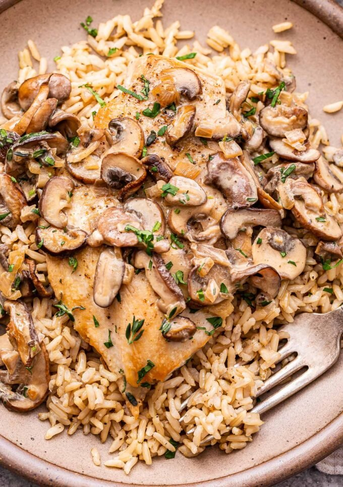 Creamy Mushroom Chicken on top of brown rice on a brown plate.