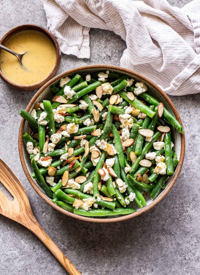Green Bean Salad with Feta and sliced almonds in a serving bowl with a wooden spoon next to it and a wooden bowl of lemon vinaigrette behind it.