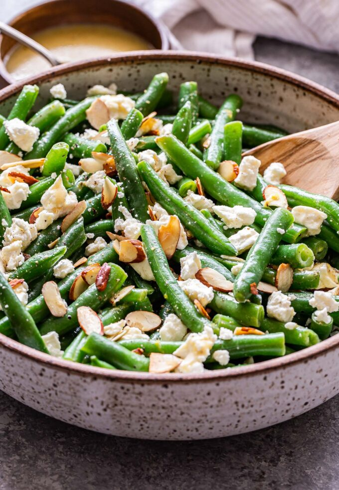 Green Bean Salad with Feta in a white serving bowl with a wooden spoon in the bowl.