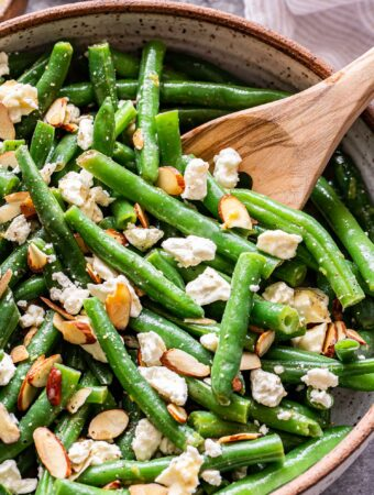 Green Bean Salad with Feta and almonds in a white bowl with a wooden serving spoon.