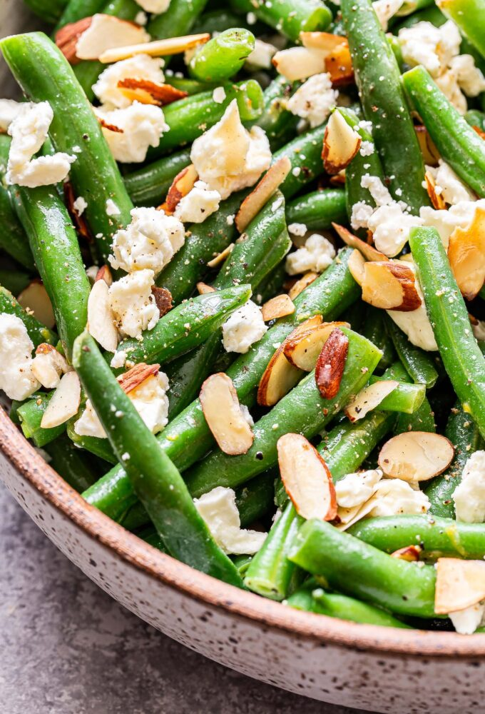 Green Bean Salad with Feta and almonds in a white serving bowl.