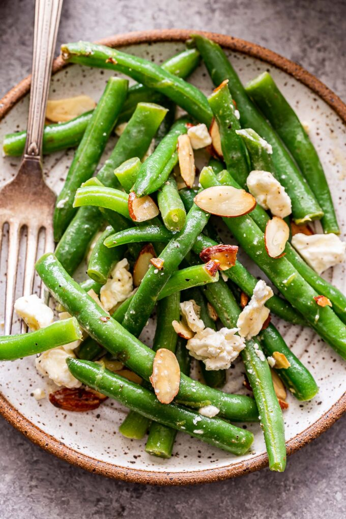 Green Bean Salad with Feta and sliced almonds on a white plate with a fork.