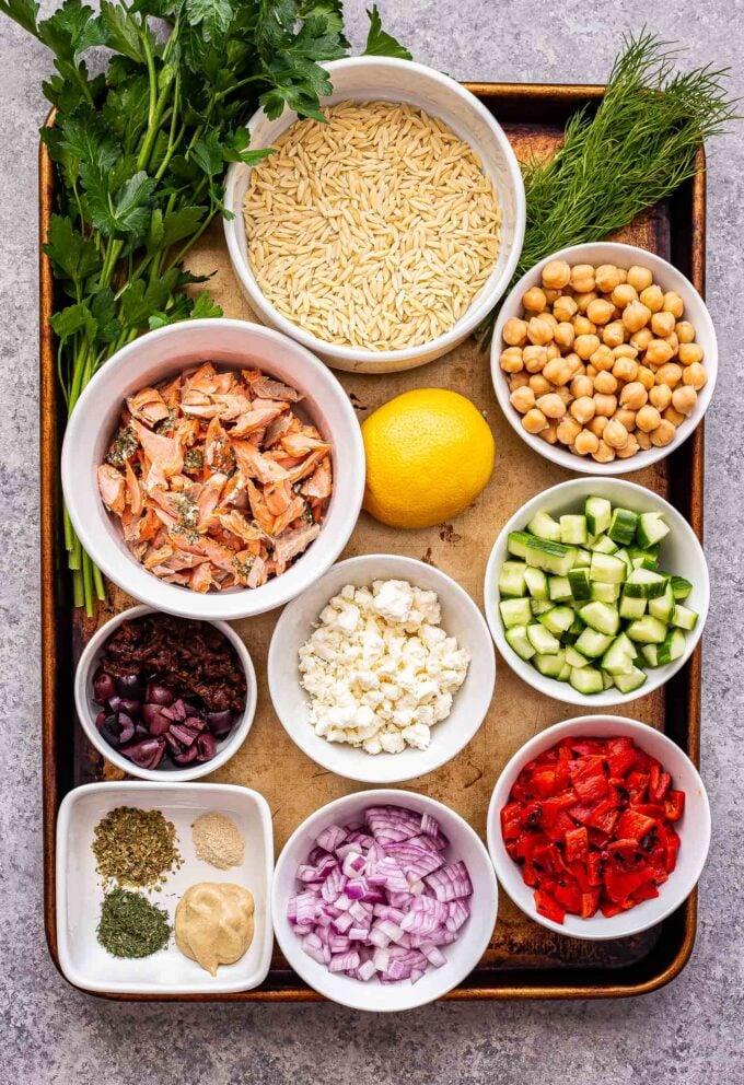 ingredients used to make Mediterranean Salmon Orzo Salad on a sheet pan.