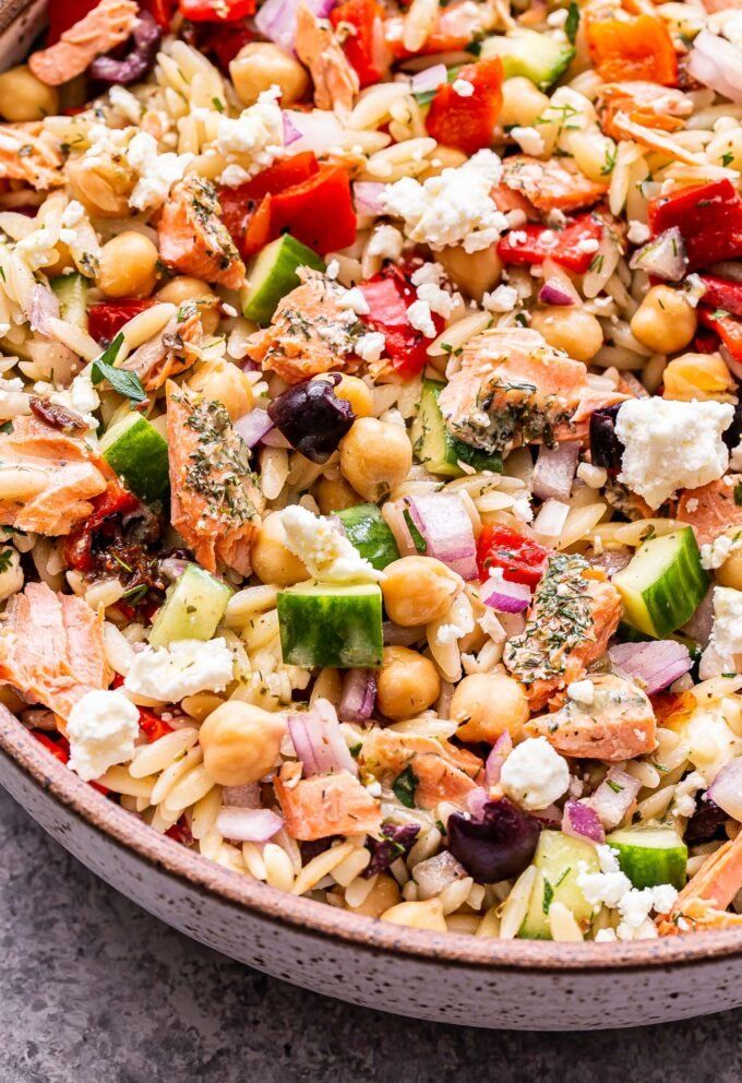 Mediterranean Salmon Orzo Salad in a white speckled serving bowl.