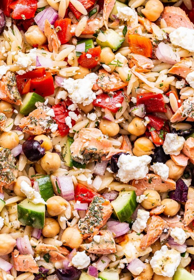 closeup photo of Mediterranean Salmon Orzo Salad with feta, chickpeas, roasted red peppers and cucumbers.