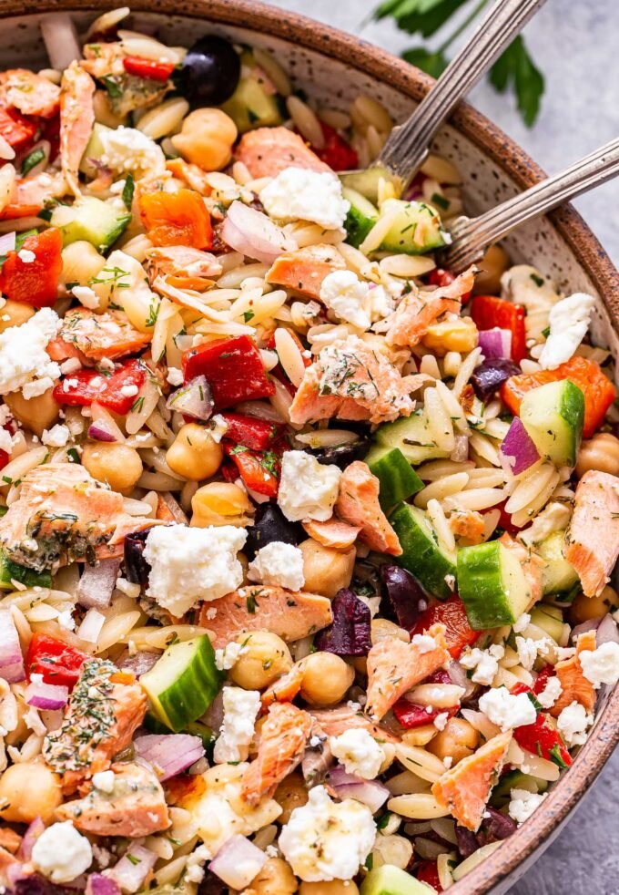 Mediterranean Salmon Orzo Salad with feta, cucumbers, roasted red peppers and olives in a white serving bowl with spoons.