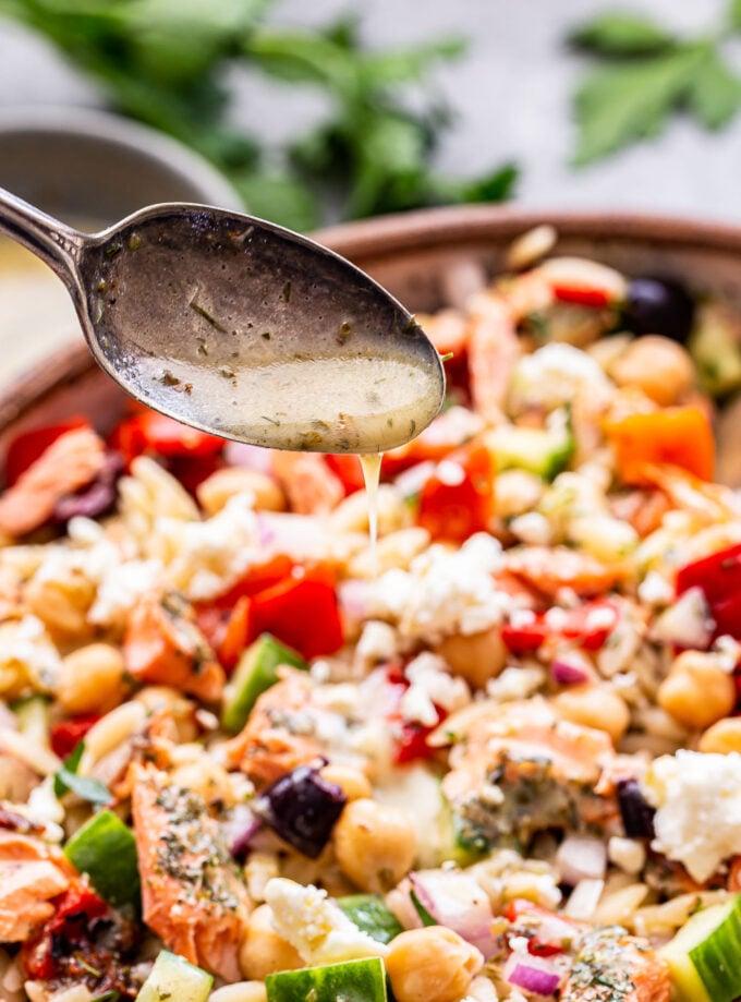 spoon pouring vinaigrette onto the Mediterranean Salmon Orzo Salad.