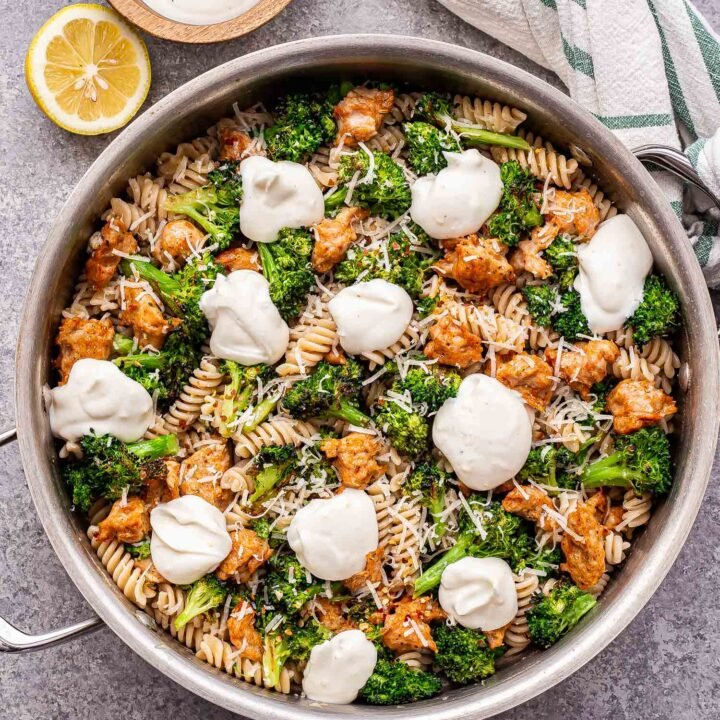 metal skillet with spicy sausage and broccoli pasta in it. Pasta topped with dollops of ricotta cheese. A small bowl of ricotta behind the skillet and half of a lemon.