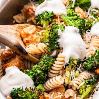 Spicy Sausage and Broccoli Pasta topped with ricotta cheese in a metal pan with a wooden spoon holding up some of it.