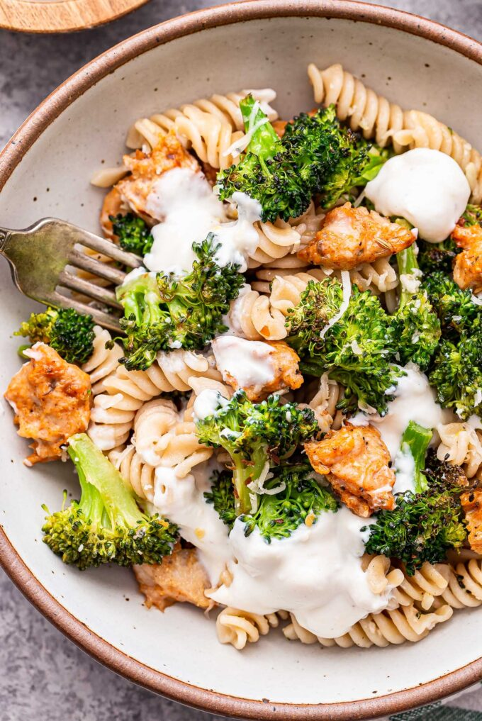 Spicy Sausage and Broccoli Pasta topped with dollops of ricotta cheese in a white bowl with a fork.