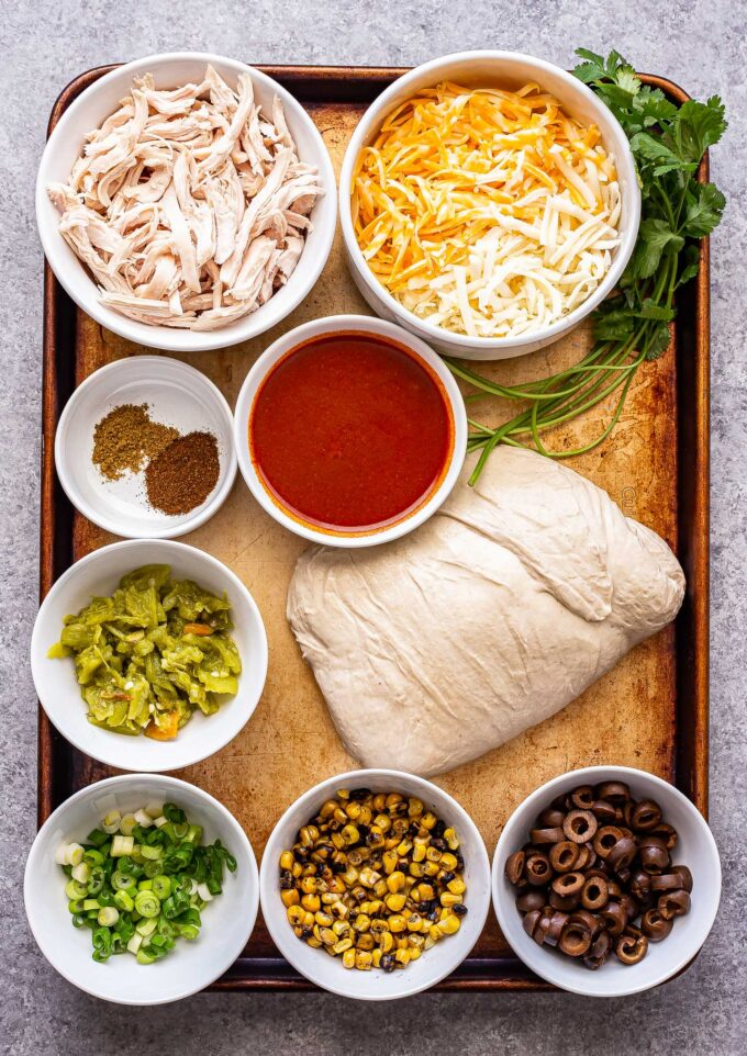 Ingredients used to make chicken enchilada pizza on a sheet pan.
