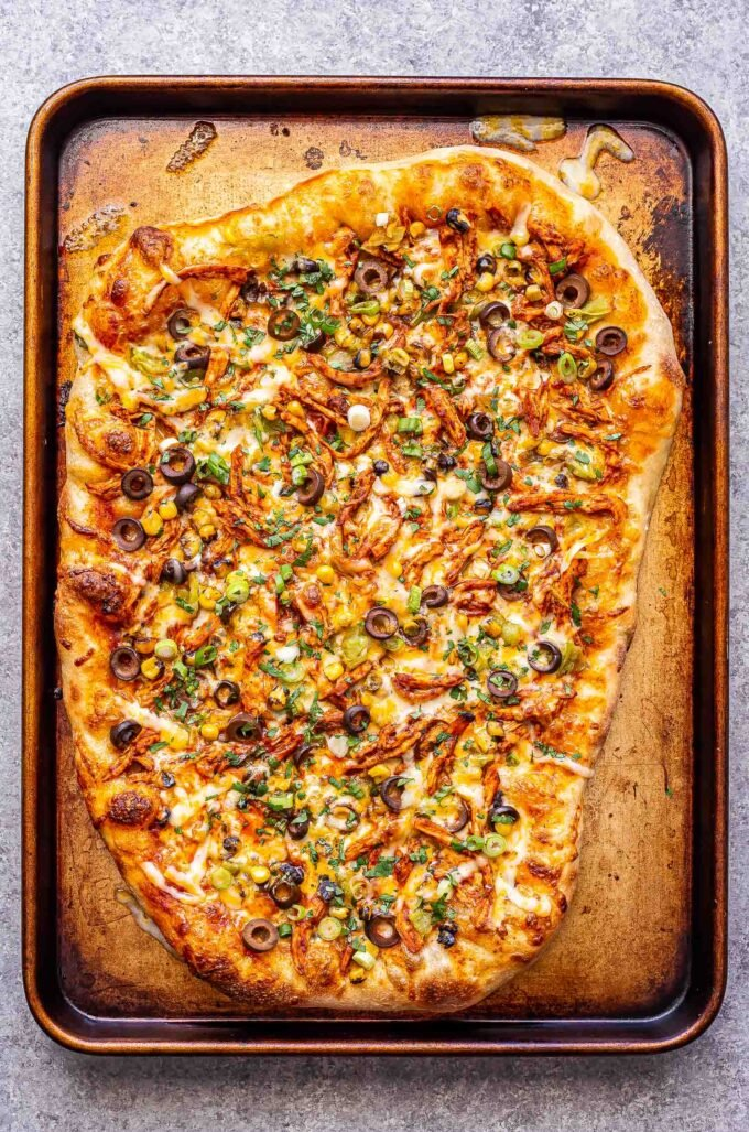 chicken enchilada pizza on a rimmed sheet pan.