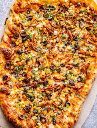 chicken enchilada pizza on a piece of parchment paper topped with corn, olives, green onions and cilantro