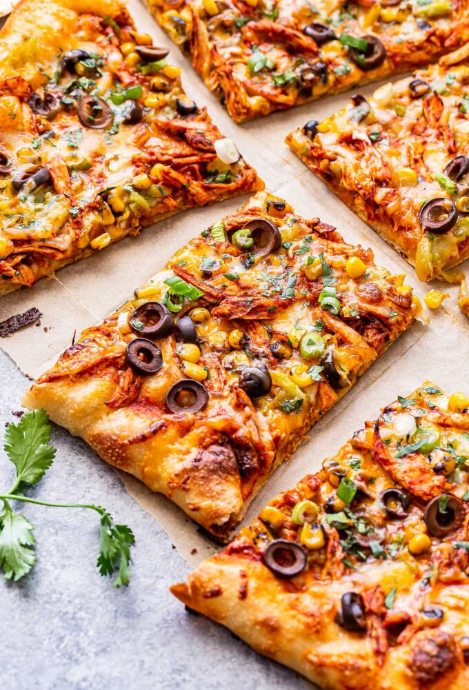 Chicken enchilada pizza cut into slices on top of parchment paper.