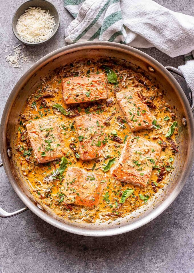Creamy Sun Dried Tomato Salmon fillets in a stainless steel pan.