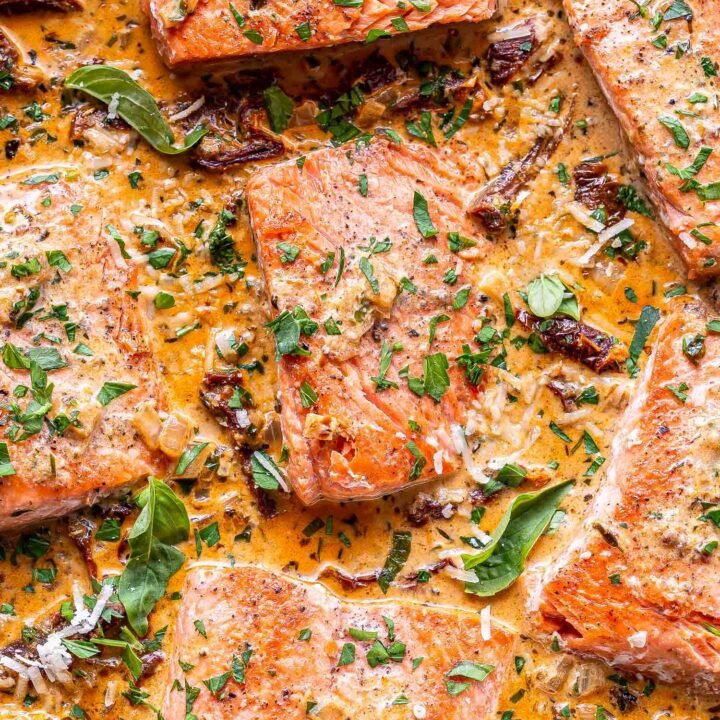 salmon fillets in a creamy sun dried tomato sauce with basil on top.