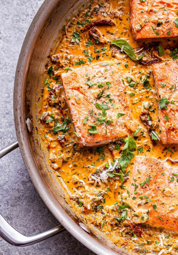 salmon fillets in a creamy sun dried tomato sauce in a stainless steel pan.