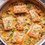 six salmon fillets in a creamy sun dried tomato sauce with a bowl of parmesan cheese behind the pan.