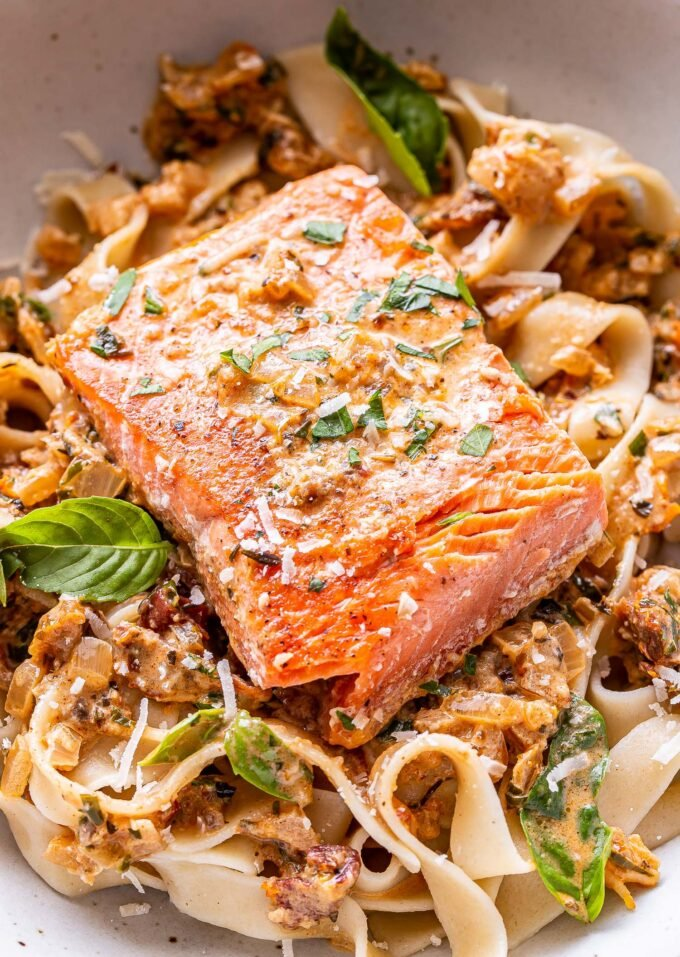 salmon fillet on top of fettuccine noodles in a sun dried tomato sauce in a white bowl.