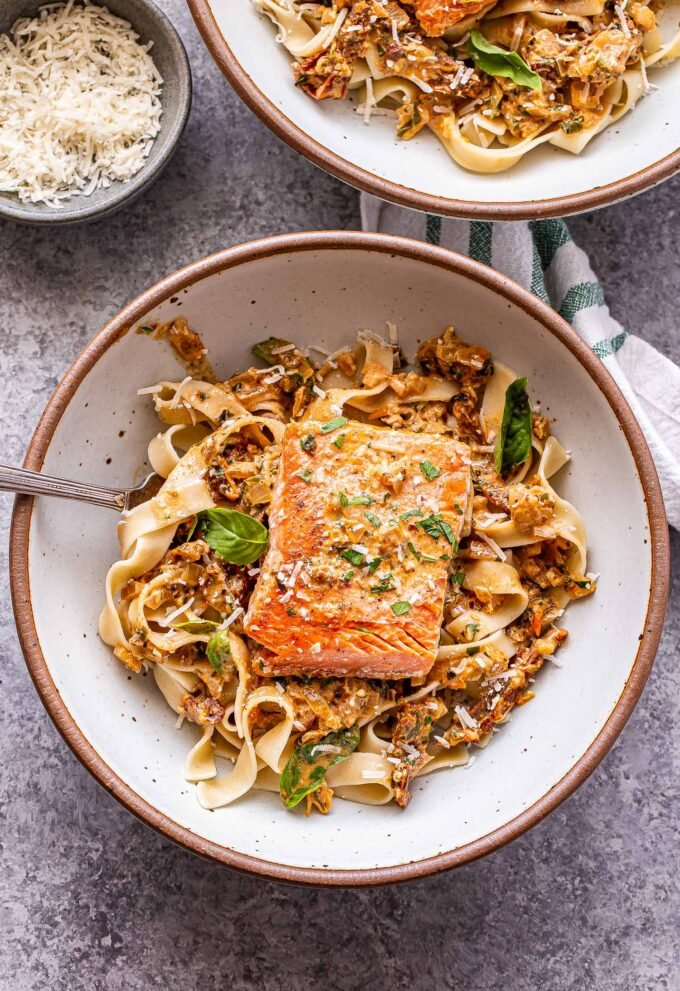 Two white bowls with Creamy Sun Dried Tomato Salmon on top of pasta.