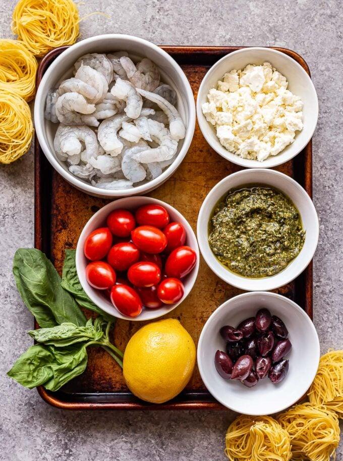 Ingredients used to make grilled shrimp pesto pasta on a sheet pan.