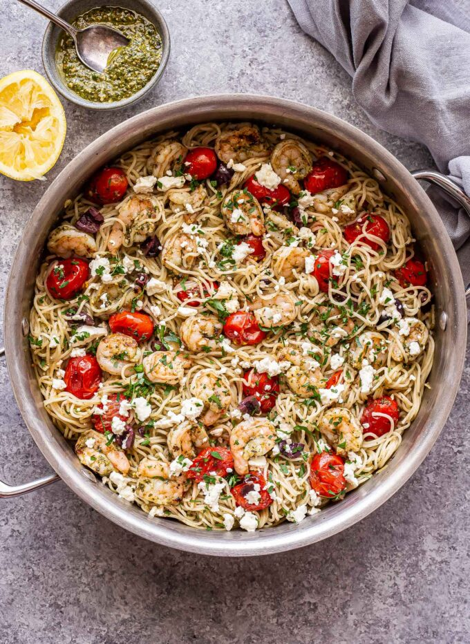 grilled shrimp pesto pasta with feta, olives, and tomatoes in a stainless steel skillet with a bowl of pesto and a lemon behind the skillet..