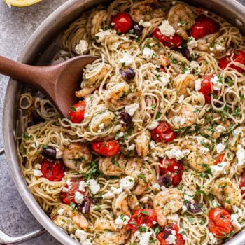 grilled shrimp pesto pasta with feta, olives, and tomatoes in a stainless steel skillet with a wooden spoon.