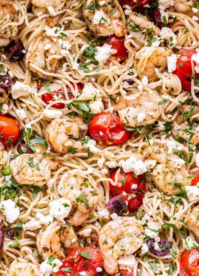 closeup photo of grilled shrimp pesto pasta with tomatoes, kalamata olives, chopped parsley and feta.