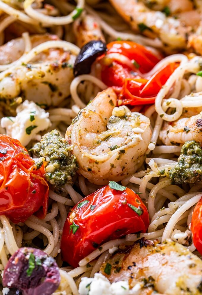 closeup photo of grilled shrimp pesto pasta with tomatoes, pesto, kalamata olives and feta.