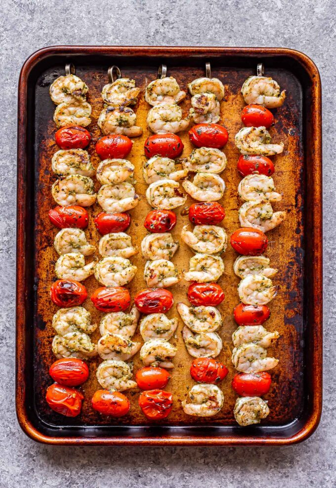 Grilled shrimp and tomatoes on skewers on a sheet pan.