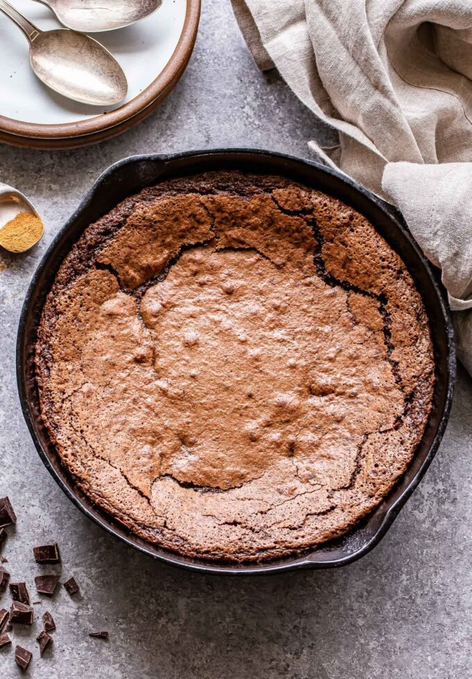 Mexican Skillet Brownies in a black cast iron skillet with a white plate and spoons behind the skillet.