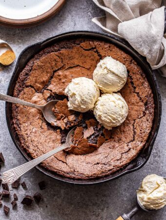 Mexican Skillet Brownies with two spoons in the skillet and three scoops of vanilla ice cream on top of them. An ice cream scoop with vanilla ice cream in it in front of the skillet.
