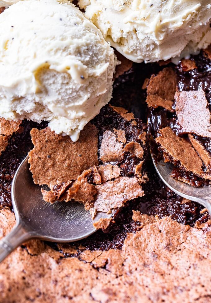 Two spoons scooping up some of the Mexican Skillet Brownies. Vanilla ice cream on top of the brownies.